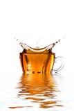Cuvette en verre de thé avec l'éclaboussure Image stock