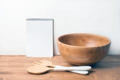 Cuvette et couverts en bois avec un carnet sur le fond ou la table en bois Arrangement naturel de table de portion Image stock
