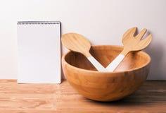 Cuvette et couverts en bois avec un carnet sur le fond ou la table en bois Arrangement naturel de table de portion Photographie stock