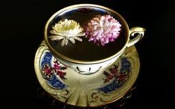 Cuvette et fleurs de thé Photo stock