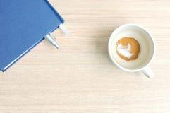 Cuvette et livre de café Photographie stock