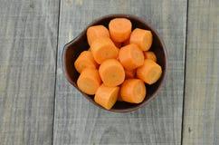 Cuvette noire avec les carottes coupées profondément sur la table en bois images libres de droits