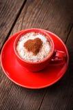 Cuvette rouge avec le cappuccino et le coeur Image stock