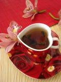 Cuvette rouge de thé sous forme de coeur avec les orchidées roses au-dessus de la paille Image libre de droits