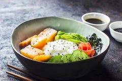 Cuvette saumonée de poussée avec du riz, les saumons, l'avocat, les graines de sésame et le concombre photographie stock