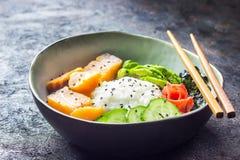Cuvette saumonée de poussée avec du riz, les saumons, l'avocat, les graines de sésame et le concombre images stock