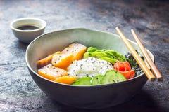Cuvette saumonée de poussée avec du riz, les saumons, l'avocat, les graines de sésame et le concombre images libres de droits
