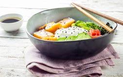 Cuvette saumonée de poussée avec du riz, les saumons, l'avocat, les graines de sésame et le concombre photographie stock libre de droits