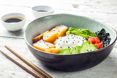 Cuvette saumonée de poussée avec du riz, les saumons, l'avocat, les graines de sésame et le concombre photos libres de droits