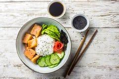 Cuvette saumonée de poussée avec du riz, les saumons, l'avocat, les graines de sésame et le concombre photo libre de droits