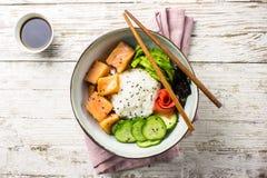 Cuvette saumonée de poussée avec du riz, les saumons, l'avocat, les graines de sésame et le concombre image libre de droits