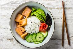 Cuvette saumonée de poussée avec du riz, les saumons, l'avocat, les graines de sésame et le concombre photos stock