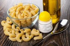Cuvette transparente avec le cavatappi cru de pâtes, macaronis, sel, cuillère, bouteille d'huile végétale sur la table en bois photo stock
