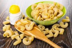 Cuvette verte avec le cavatappi cru de pâtes, macaronis dans la cuillère, dispositif trembleur de sel sur la table en bois images libres de droits