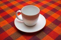 Cuvette vide de café sur un tissu checkered Images libres de droits