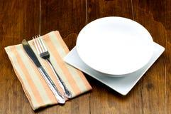 Cuvette vide sur le plat carré avec la fourchette et couteau sur le fond en bois Photos libres de droits