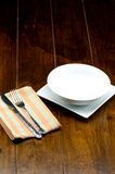 Cuvette vide sur le plat carré avec la fourchette et couteau sur le napery Photographie stock libre de droits