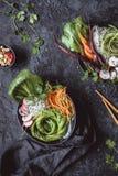Cuvettes asiatiques délicieuses avec des nouilles, des légumes et des graines de sésame de riz sur le fond noir Vue supérieure image stock