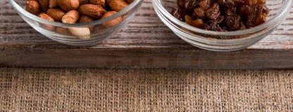 Cuvettes avec des raisins secs, arachides et sur la table en bois Vue supérieure Copiez l'espace endroit pour votre inscription image stock