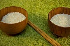 Cuvettes avec du riz et des bâtons sur le vert Photographie stock libre de droits