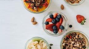 Cuvettes avec du yaourt, la granola et les diff?rents fruits sur le fond blanc photographie stock libre de droits
