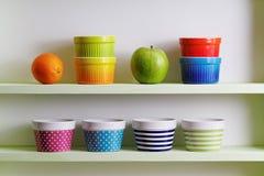 Cuvettes colorées sur une étagère de cuisine Photo stock