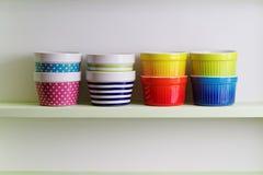 Cuvettes colorées sur une étagère de cuisine Photographie stock libre de droits