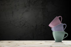 Cuvettes de café colorées sur la table en bois Images stock