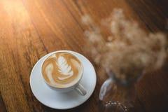 Cuvettes de café et grains de café frais autour Photo stock