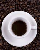 Cuvettes de café sur des haricots Photographie stock libre de droits