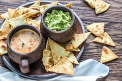Cuvettes de guacamole et de queso avec des puces de tortilla Photo stock