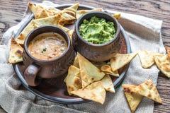 Cuvettes de guacamole et de queso avec des puces de tortilla Photographie stock libre de droits
