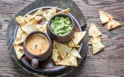 Cuvettes de guacamole et de queso avec des puces de tortilla Photos stock