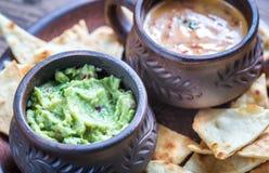 Cuvettes de guacamole et de queso avec des puces de tortilla Images stock