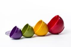 Cuvettes de mesure colorées dans la taille croissante sur le blanc Photo stock