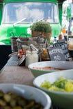 Cuvettes de nourriture et de pots de sauce sur une table avec un camion au b Images libres de droits