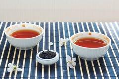 Cuvettes de thé, choc de feuilles de thé et fleurs de cerise Image stock