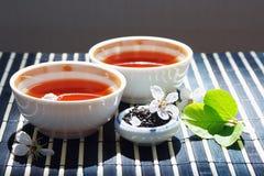 Cuvettes de thé, choc de feuilles de thé et fleurs de cerise Photos stock