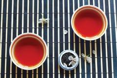 Cuvettes de thé, choc de feuilles de thé et fleurs de cerise Images stock
