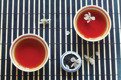 Cuvettes de thé, choc de feuilles de thé et fleurs de cerise Image libre de droits