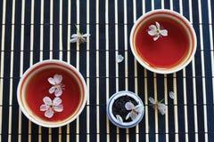 Cuvettes de thé, choc de feuilles de thé et fleurs de cerise Photos libres de droits
