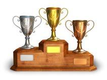 Cuvettes de trophée d'or, d'argent et de bronze sur le pupitre Photographie stock libre de droits