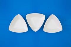Cuvettes en céramique triangulaires vides pour des sushi sur le tabl en bois bleu Photo libre de droits