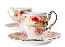 Cuvettes et soucoupes de café décorées des fleurs Photographie stock
