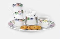 Cuvettes, un bol de sucre, une plaque et quelques biscuits Images libres de droits