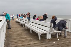 People at wooden pier Cuxhaven waiting for ferry to Helgoland. Stock Photo