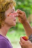 CUYABENO,厄瓜多尔06日2017年:未认出的旅游绘画她的使用achiote种子的面孔从这些多刺的红色荚 库存图片