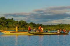 CUYABENO,厄瓜多尔- 2016年11月16日:准备好年轻的游人跳进盐水湖重创反对日落, Cuyabeno 免版税库存照片
