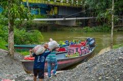 CUYABENO,厄瓜多尔- 2016年11月16日:拿着他的肩膀大袋的未认出的人民对小船,在亚马逊里面 库存照片