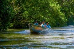 CUYABENO,厄瓜多尔- 2016年11月16日:旅行乘小船的未认出的人民入亚马逊密林的深度  免版税库存照片